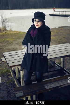 Temerosos de la moda mujer vistiendo un abrigo y sombrero y ella posando en una playa invernal, frío lluvioso, Cruz imagen procesada