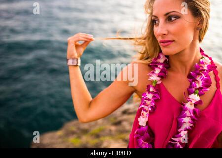 Mujer caucásica relajante sobre rocas en la playa Foto de stock