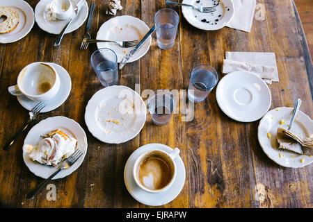 Platos vacíos, las tazas de café y vasos sobre la mesita de café