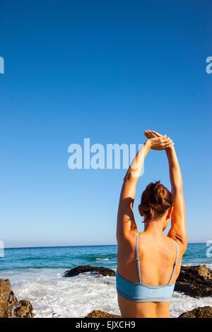 Mujer estirando los brazos en la playa, vista posterior