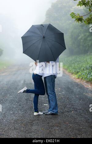 Romántica pareja joven escondiéndose detrás de los paraguas en la lluvia