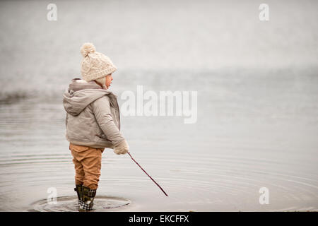 Joven de pie en un lago, sosteniendo un palo