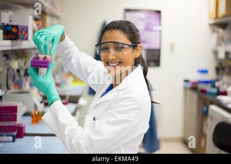 Closeup retrato, Young Scientist en blanco y gafas labcoat haciendo experimentos en laboratorio, sector académico.