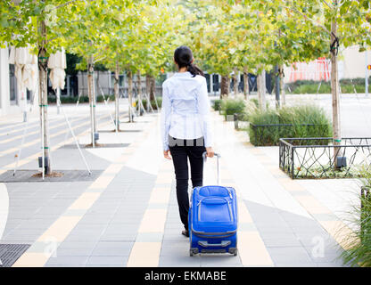 Vista posterior abstracto Closeup retrato de mujer en camisa azul claro llevar equipaje, caminando por el verde de los árboles en la acera gris