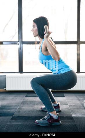 Vista lateral el retrato de una mujer joven haciendo flexiones con barbell en el gimnasio
