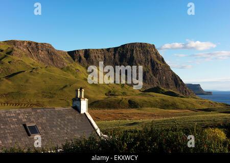 Mirando por encima de una casa, hacia Waterstein Head desde la carretera de camino a Neist Point faro en la Isla Foto de stock
