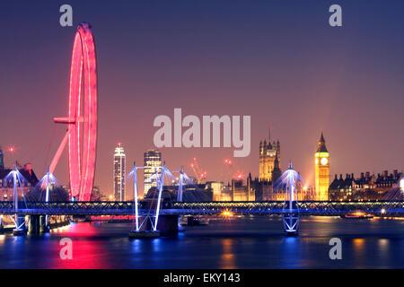 Londres de noche. El London Eye y el puente Hungerford del Jubileo de Oro de puentes y Palacio de Westminster con Foto de stock