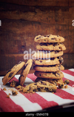 Pila de galletas con trocitos de chocolate en rojo y raya blanca servilleta contra un fondo de madera oscura.