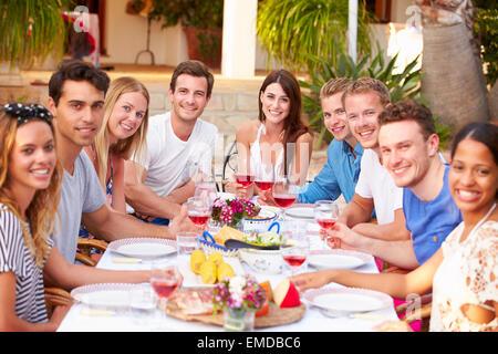 Grupo numeroso de jóvenes amigos, disfrutando de comidas al aire libre juntos