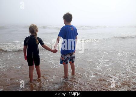 Un chico y una chica cogidos de la mano mire hacia el mar en un día brumoso