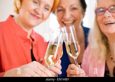 Tres Amigos Mamá sonriente Tossing copas de champaña celebrando su amistad. Capturado en Macro.