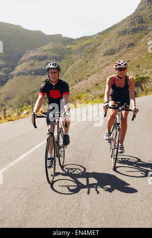 Par de ciclistas en bicicleta en una carretera. Colocar jóvenes en bicicleta cuesta abajo. En el camino de preparación de la carrera de triatlón.