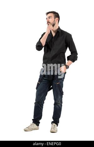 Cool moda joven hombre que toca su barba mirando a otro lado. Longitud de cuerpo completo retrato aislado sobre fondo blanco. Foto de stock