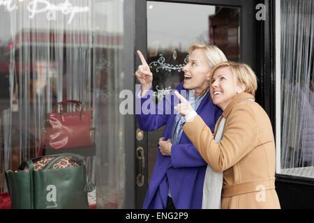Las mujeres de raza blanca mayores de escaparates en la tienda de ropa