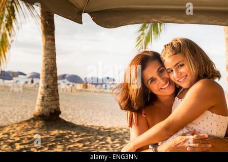 Madre e hija abrazarse bajo las sombrillas de playa