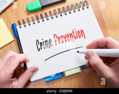 Un empresario por escrito las palabras, la prevención del delito, en un bloc de notas.
