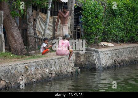 India, Kerala, Alleppey. Canales de remanso de Kerala en el área de Kumarakom, conocida como la 'Venecia de Oriente'. Mujer pesca.