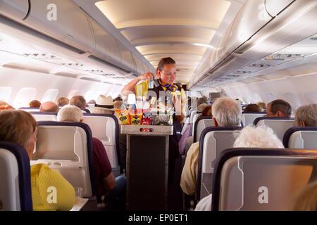 Una azafata miembro de la tripulación de cabina, sirviendo comida en un Monarch Airlines avión desde Madeira hasta el aeropuerto de Gatwick, REINO UNIDO