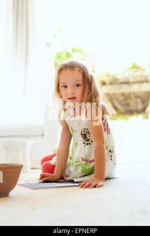 Retrato de cute little girl dibujo mientras está sentado en el piso en su casa mirando a la cámara. Edad elemental joven sentado en livi