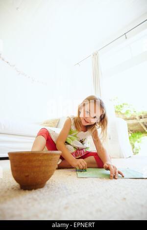 Retrato de Niña preescolar imagen colorear en el piso de su casa. Niña sentada en el suelo pintar un cuadro.