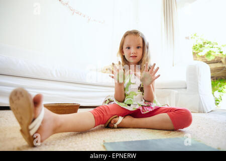 Retrato de hermosa niña divirtiéndose mientras la pintura. Colegiala sentada en el piso en casa mostrando sus palmas pintadas.