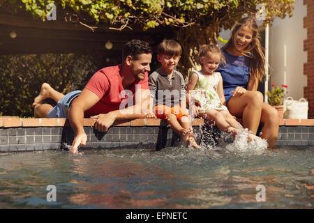 Familia caucásica divirtiéndose en la piscina de su casa. Feliz familia joven salpicaduras de agua con las manos y las piernas mientras está sentado en el borde