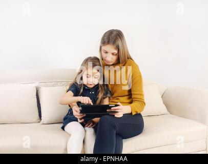 Niña con su madre utilizando dispositivo tableta en el sofá en casa, familia feliz, concepto tecnológico
