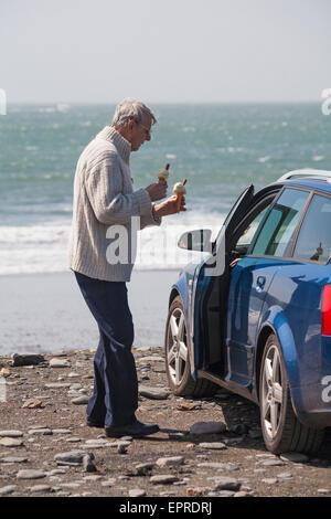 Hombre tomando dos helados con copos de vuelta al coche en Abereiddy, Pembrokeshire Coast National Park, Wales, Reino Unido en mayo Foto de stock