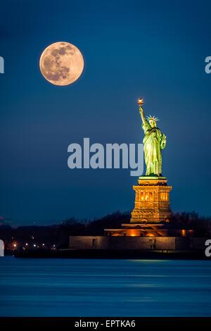 Estatua de la libertad y un aumento en la Ciudad de Nueva York supermoon Foto de stock