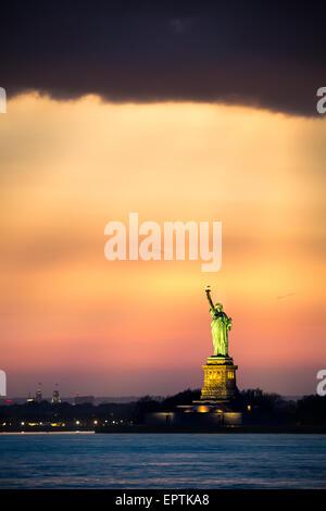 La estatua de la libertad bajo una espectacular luz del atardecer visto desde el puente de Brooklyn, Nueva York Foto de stock