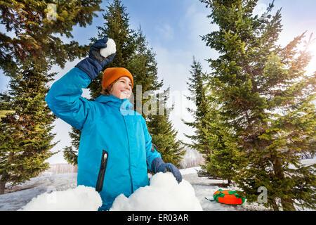 Muchacho feliz listo para lanzar bola de nieve en el bosque