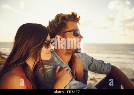 Hermosa pareja joven junto al aire libre en un día de verano. Pareja caucásica disfrutando de la vista a la playa, ambos con gafas de sol.