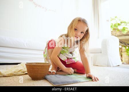 Retrato de niña inocente pintar un cuadro. Colegiala sentada en el suelo colorear sonriendo mirando a la cámara.