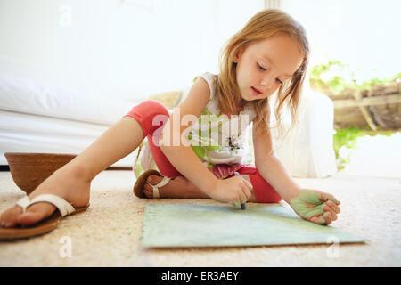 Foto de cute little baby girl colorear la imagen mientras está sentado en el suelo en casa.