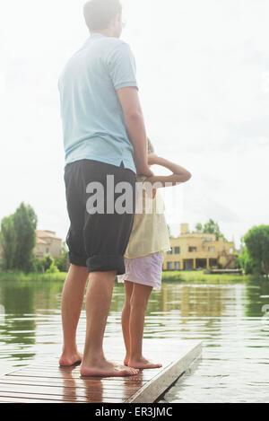 El padre y la hija juntos al final del lago muelle mirando a ver