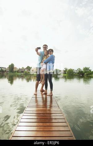 Familia con hija joven de pie junto al final del lago pier teniendo selfie