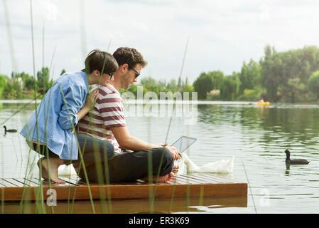 Pareja utilizando equipo portátil en el dock