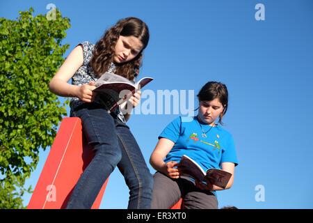 Hay Festival, Powys, Gales - Mayo de 2015 - Dos niñas libros de lectura en la parte superior del gigantesco cartel Foto de stock