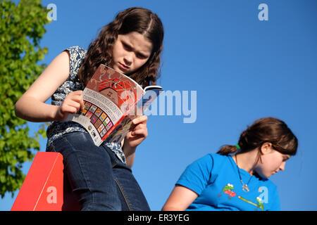 Hay Festival, Powys, Gales - Mayo 2015 - Niña leyendo un libro sentado en la parte superior del gigantesco cartel Foto de stock