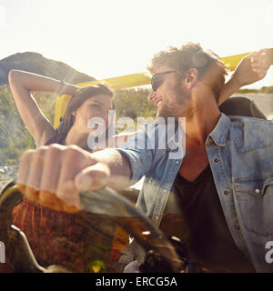 Feliz el hombre y la mujer joven en un coche, disfrutando de un viaje por carretera en un día de verano. Par en Foto de stock