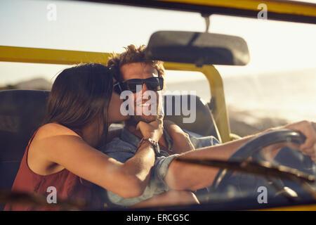 Joven pareja amorosa en viaje por carretera. Mujer besar las mejillas de su novio. Joven conduciendo un coche. Romántica pareja joven disfrutando
