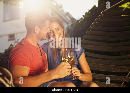Hermosa joven pareja vino tostado en el exterior. Están sentados en una hamaca sonriendo y bebiendo vino con luz solar brillante en b