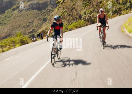 Dos ciclistas practicando para triatlón de la raza. Triatletas practicar ciclismo en carretera. El hombre y la mujer que monta a bicicleta en abrir