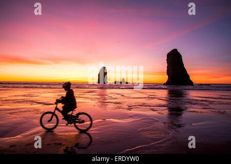 Silueta de niña caucásica ciclismo cerca de formaciones rocosas en Cannon Beach, Oregon, Estados Unidos Foto de stock