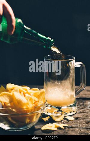 Echando mano de vaso de cerveza cerca de papas fritas