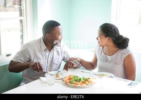 Pareja sonriente comiendo juntos en la mesa