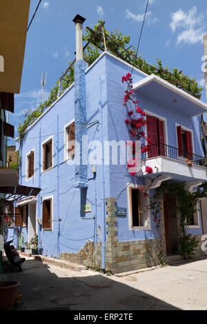 Casa pintada de azul con rojo buganvilla florece en la ciudad de Chios, en la isla de Chios, Grecia