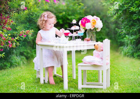 Niñito adorable chica con el pelo rizado con un colorido vestuario en el día de su cumpleaños jugando tea party con un oso de peluche doll