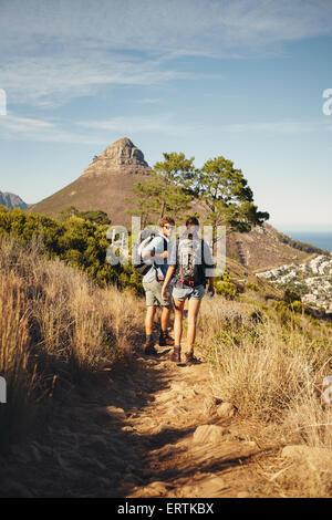 Retrato de un par de excursionistas caminando por camino de montaña. Un hombre y una mujer disfrutando de las vacaciones Foto de stock