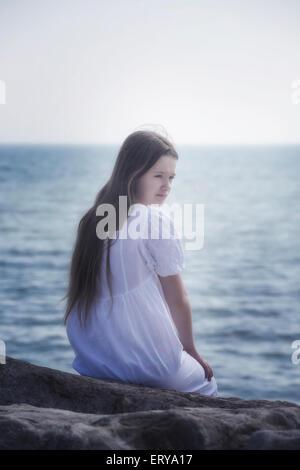 Una niña en un vestido blanco sentada sobre las rocas en el mar